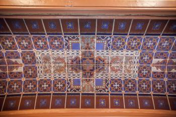 The polychrome ceiling, which has an appearance of tiles, is actually painted gauze over a thick layer of felt
